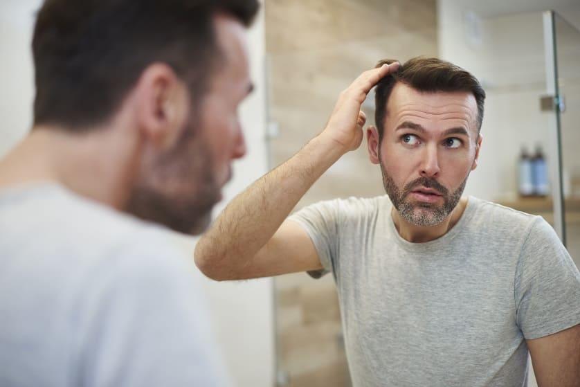 Mann steht vor dem Spiegel und macht sich Sorgen um seinen Haarausfall