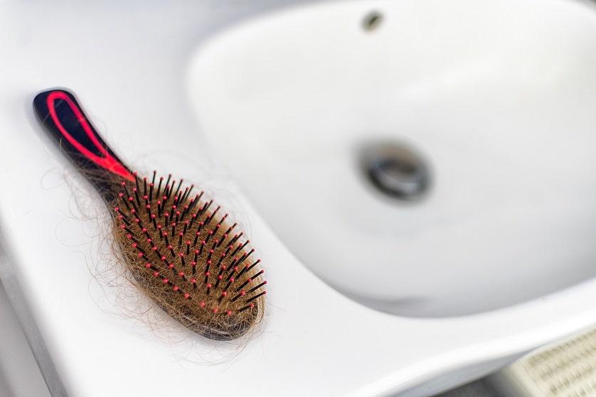 ausgefallene Haare hängen in der Bürste