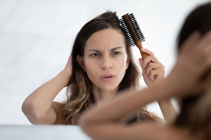 Frau kämmt sich die Haare und schaut dabei unzufrieden in den Spiegel