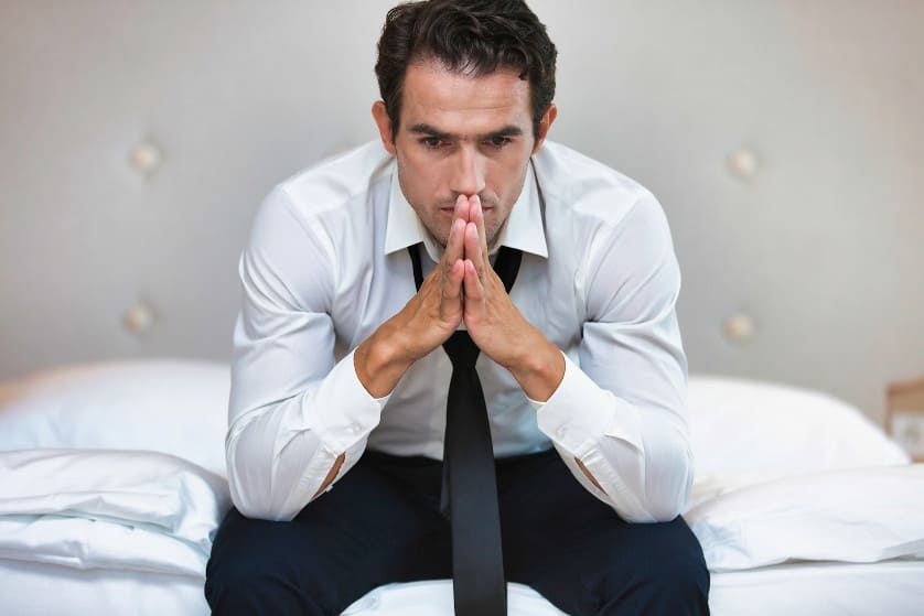 Gestresster Businessmann sitzt auf dem Bett