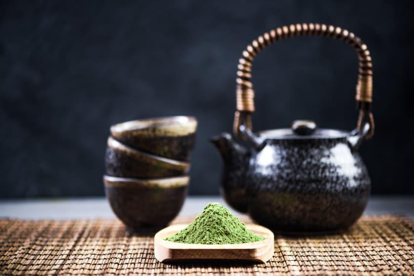 Grüntee Pulver vor einer Teekanne