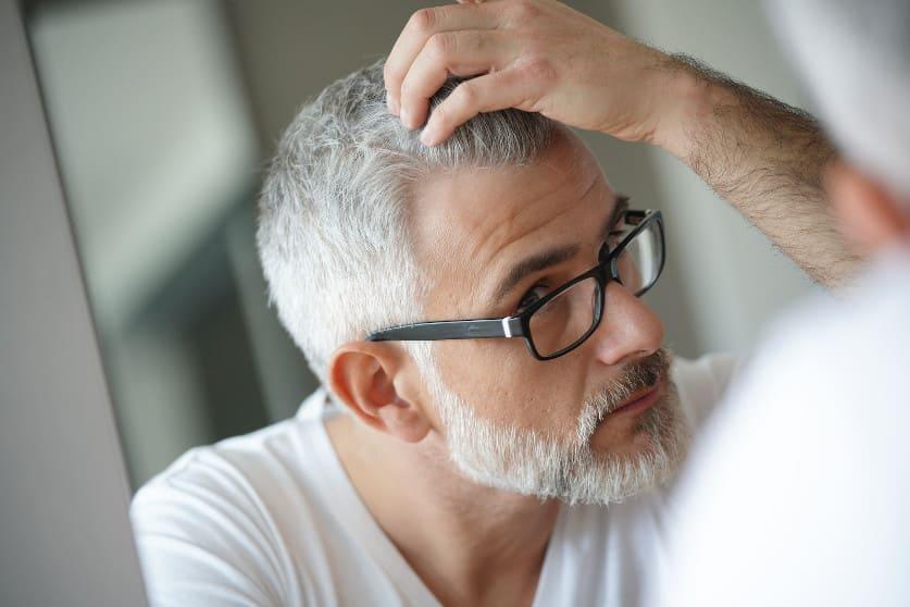 Älterer Mann begutachtet seinen Haarausfall im Spiegel
