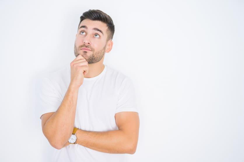 Junger Mann steht vor weißem Hintergrund und grübelt über eine Frage nach