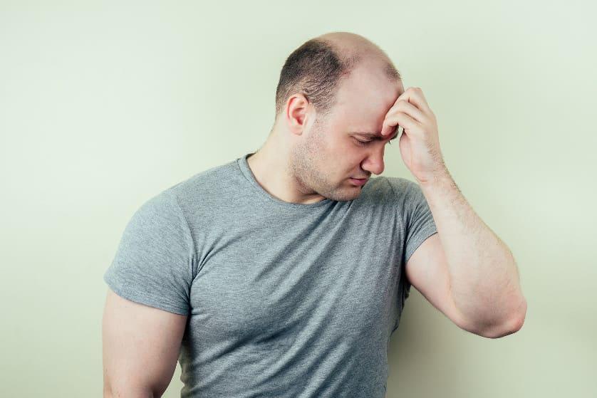 Mann überlegt sich erste Schritte gegen Haarausfall