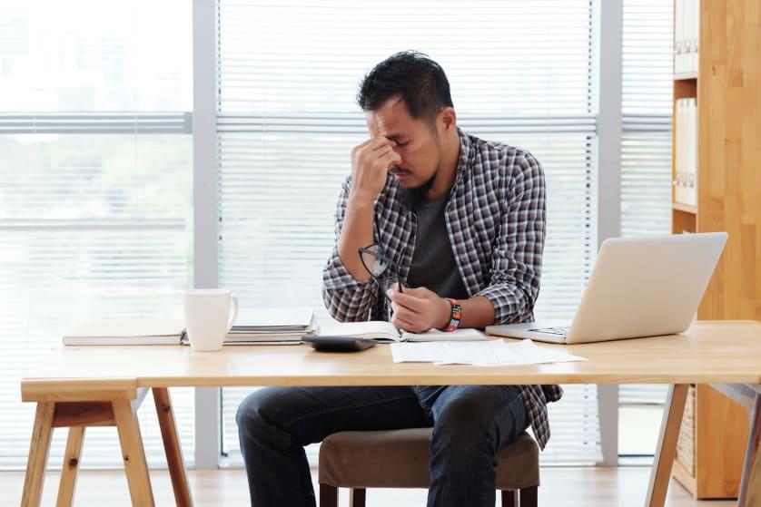 Mann sitzt vor seinem Laptop und ist gestresst