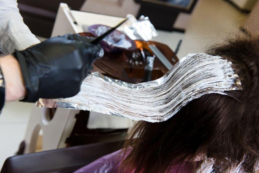 Frau sitzt beim Frusör und lässt sich die Haare tönen