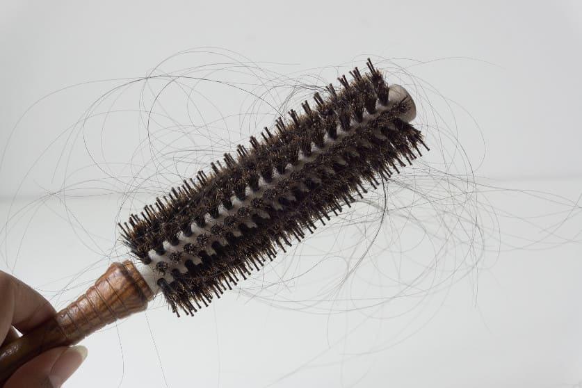 Nahaufnahme eines Kamms indem ein Büschel Haare hängt
