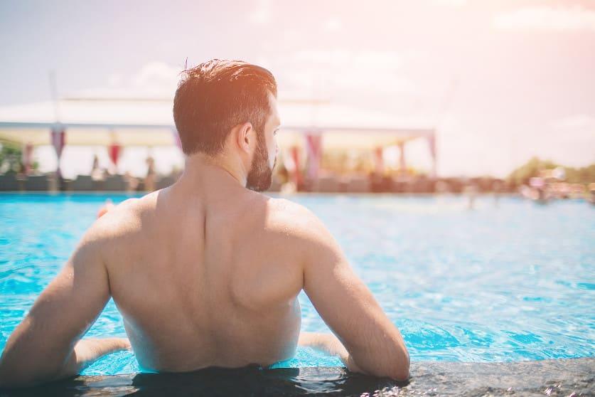 Mann sitzt im Pool und denkt über Haarausfall durch Chlor