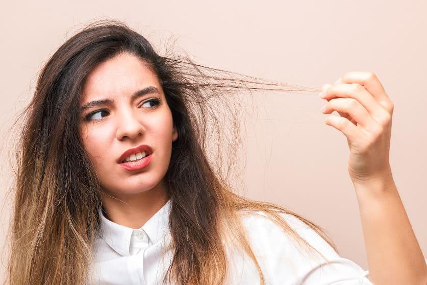 Junge Frau ist erschrocken über ihre trockenen Haare