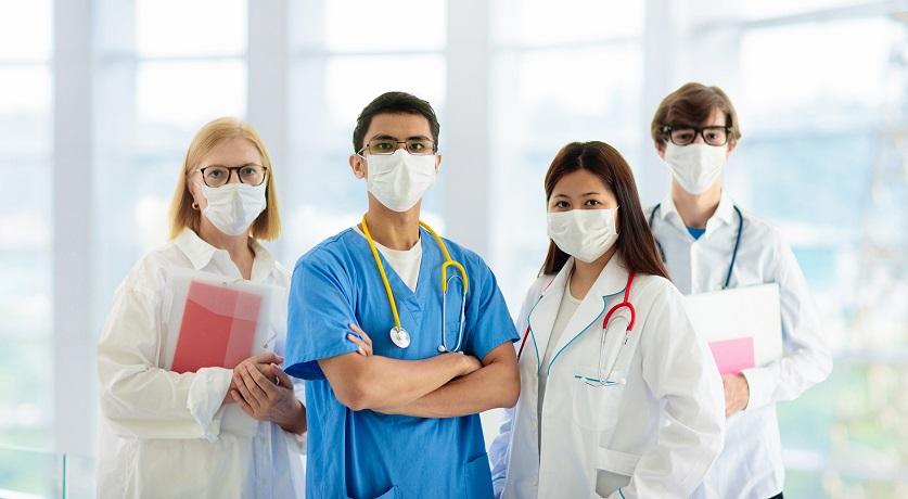 Internationales Team an Ärzten mit Mundschutz und Stethoskop stehen in der Lobby eines Krankenhauses