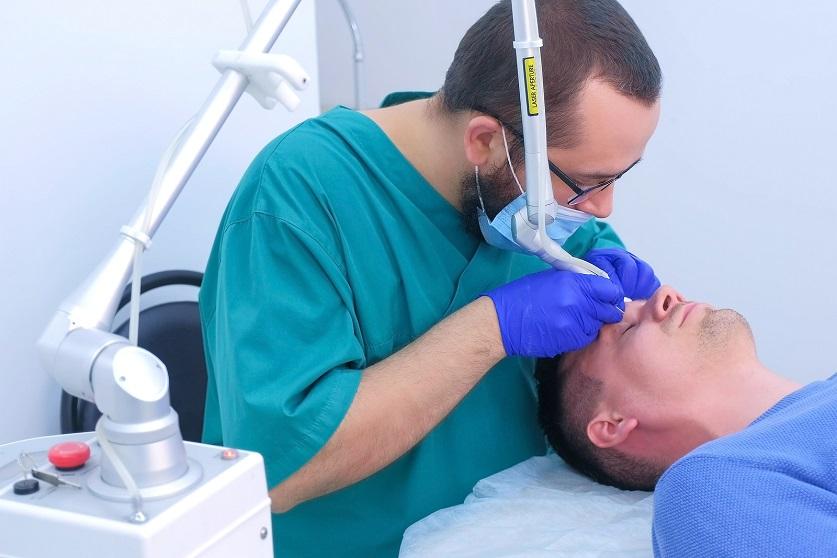 Arzt lasert die Augen eines Patienten