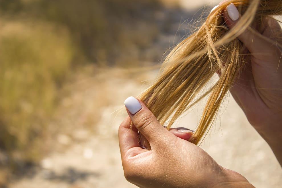 Frau hält ihre brüchigen Haare in der Hand