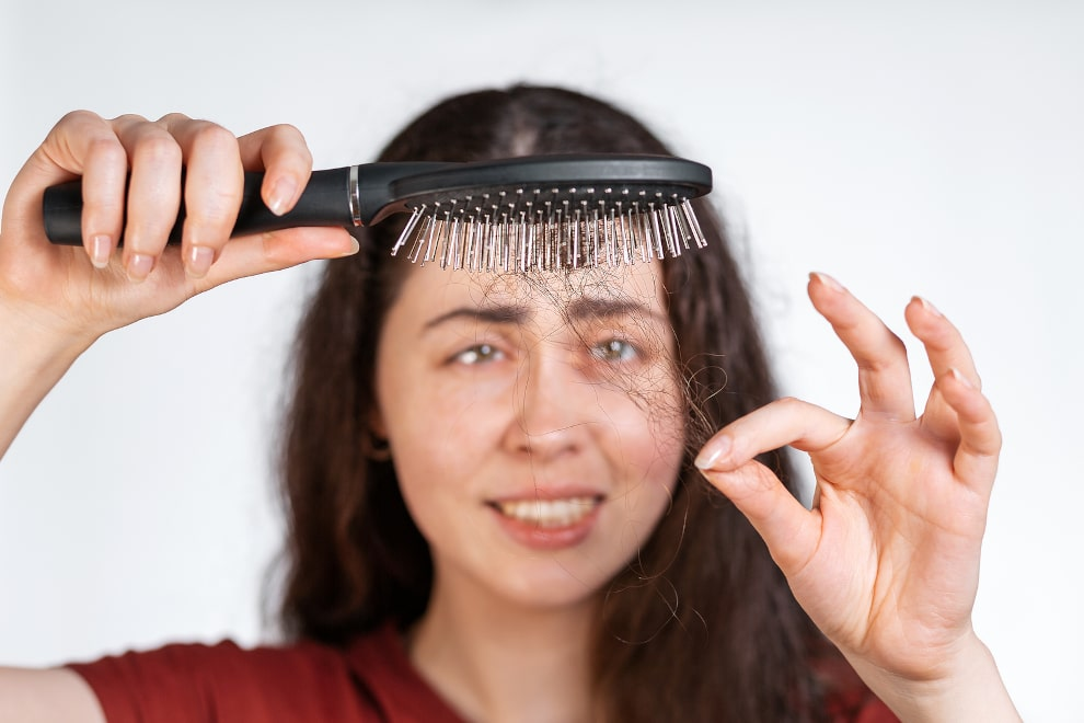 Brünette Frau hält eine Bürste mit ausgefallenen Haaren in den Vordergrund
