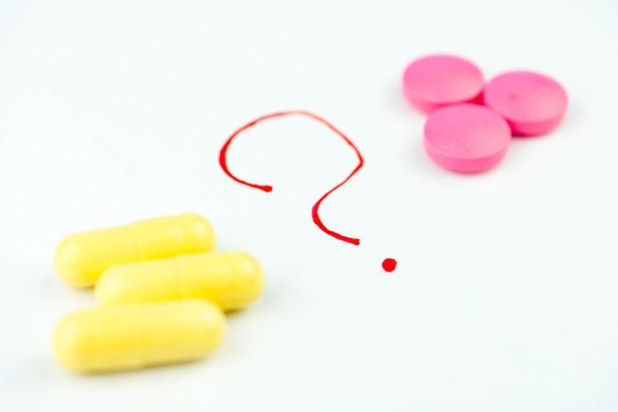 Gelbe und pinke Pillen liegen auf einem weißen Hintergrund zwischen einem aufgemaltem Fragezeichen