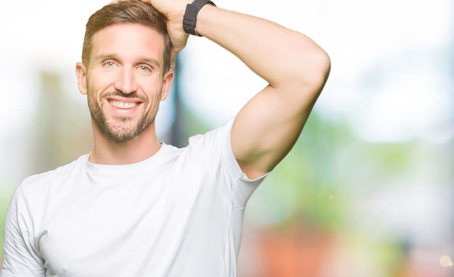 Mann fässt sich ins Haar und lächelt dabei