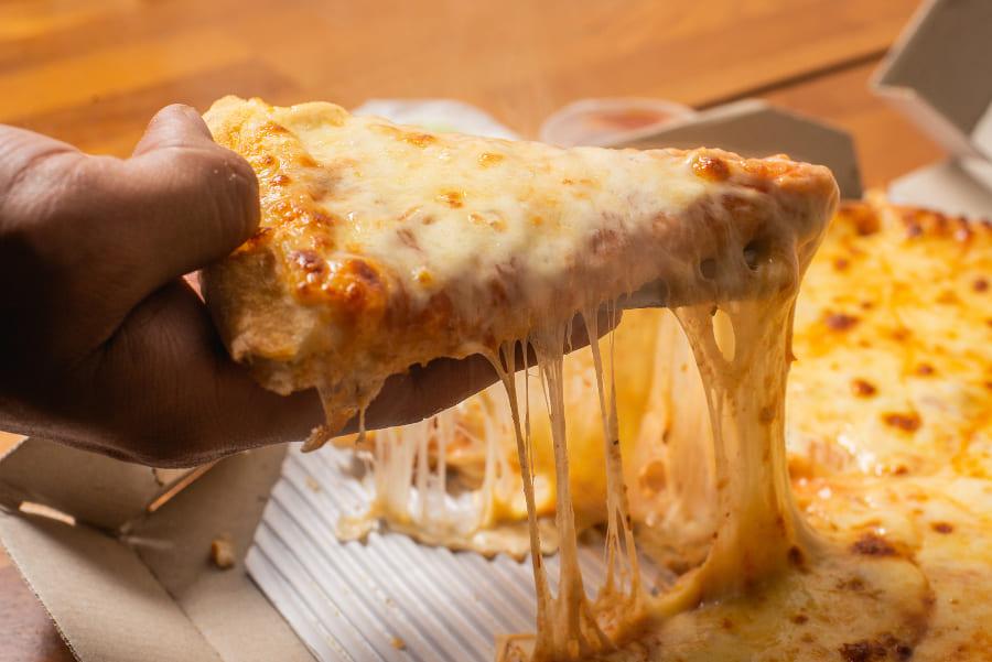 Pizza mit viel Käse auf einem Tisch