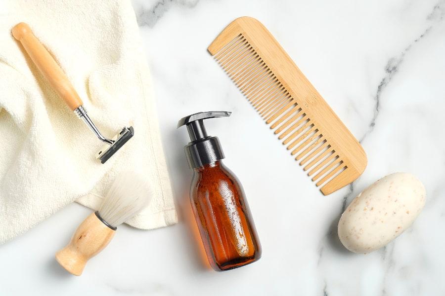 Eine Tinktur gegen Kopfhaut Pilz und Haarausfall liegt neben Kamm und Rasierer