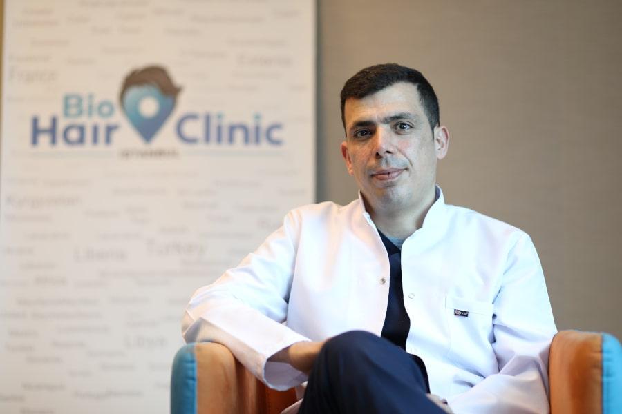 Dr.Ibrahim sitzend vor dem Bio Hair Clinic Banner