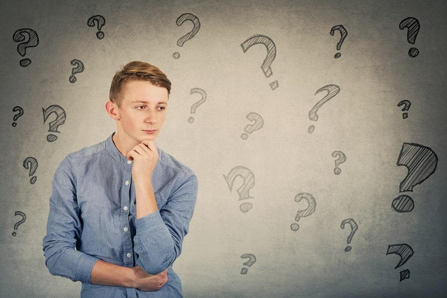 Junge hat die linke Hand am Kinn und schaut fragend in den Raum während animierte Fragezeichen um ihn herum schweben