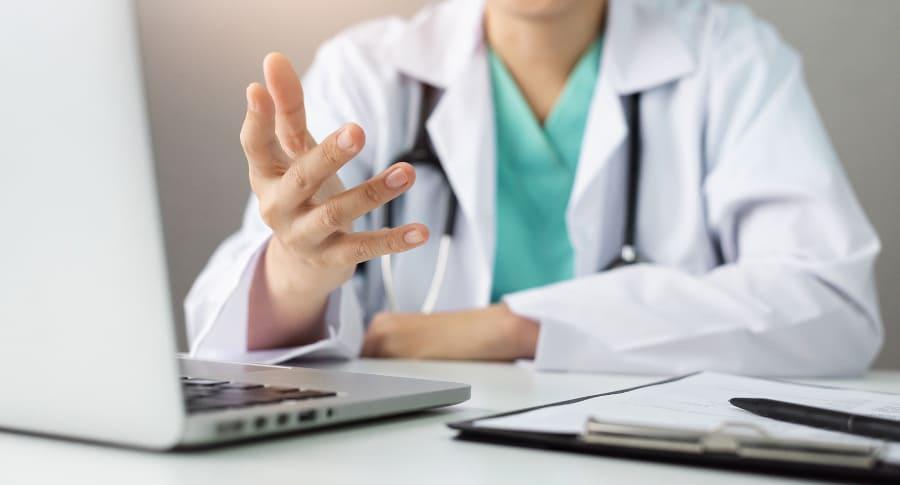 Arzt sitzt am Schreibtisch und streckt seine hand fragend vor sich