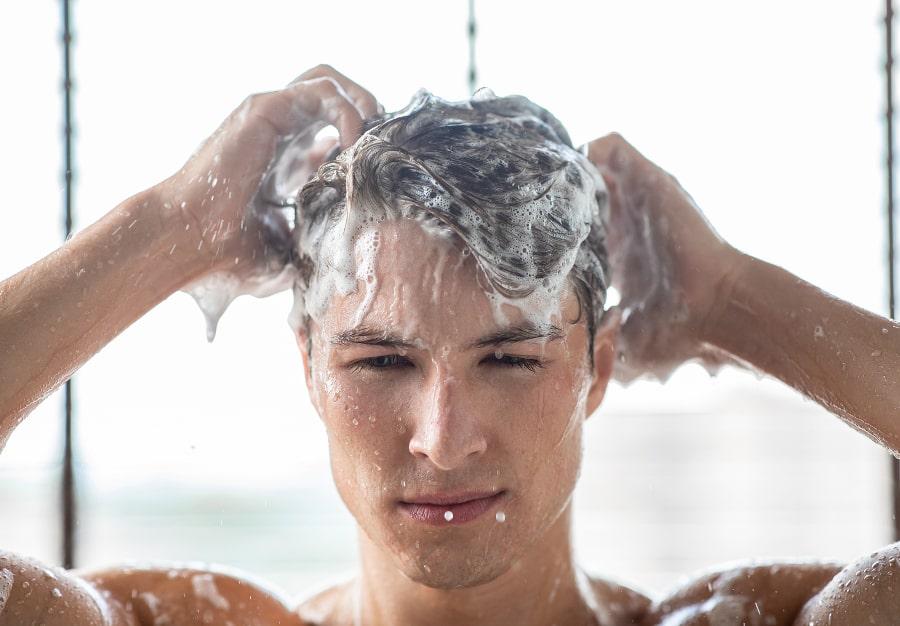 Nahaufnahme von jungem Mann bei Haarwäsche mit Kopfhaut Pilz Haarausfall