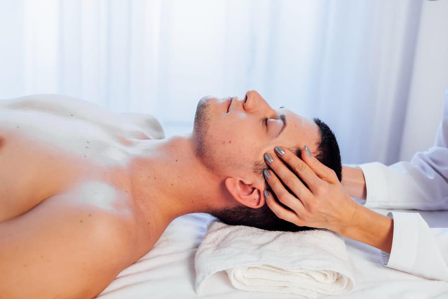 Mann liegt mit verschlossenen Augen auf dem Rücken und bekommt eine Kopfmassage