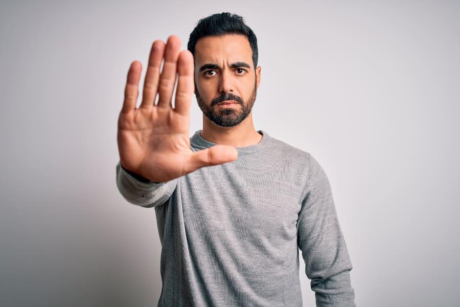 Mann streckt offene Hand nach vorne und hat ein ernstes Gesicht