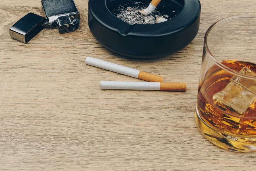 Zigaretten, Aschenbecher, Feuerzeug und ein Glas gefüllt mit Alkohol liegen auf einem Holztisch