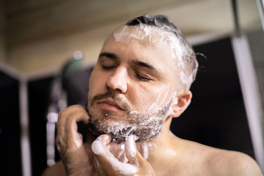 Mann wäscht seine Haare und seinen Bart mit Seife