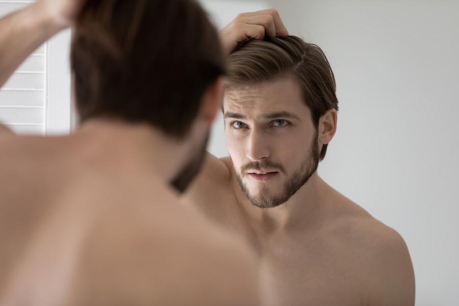 Mann mit Haarverlust schaut sich im Spiegel an