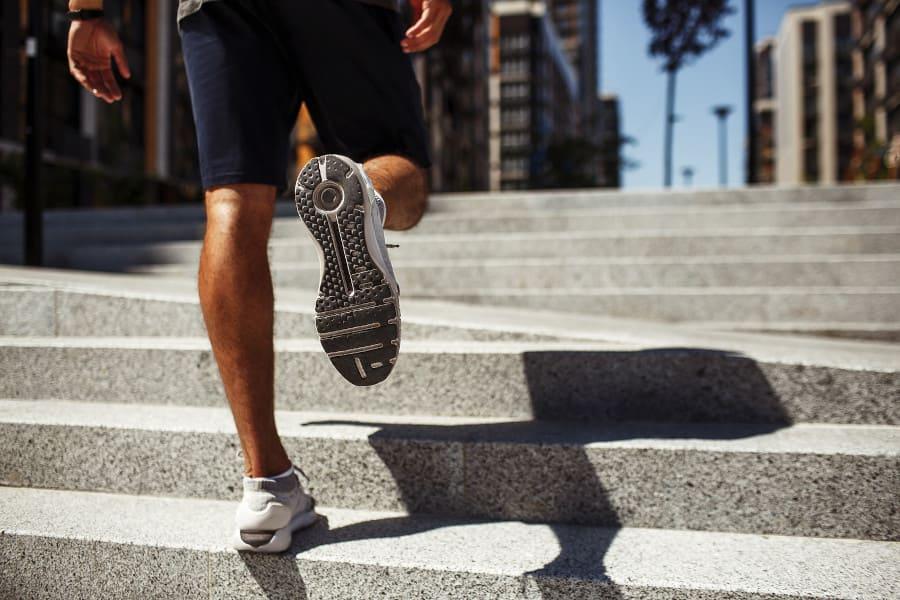 Mann läuft Treppe in Laufschuhen hoch