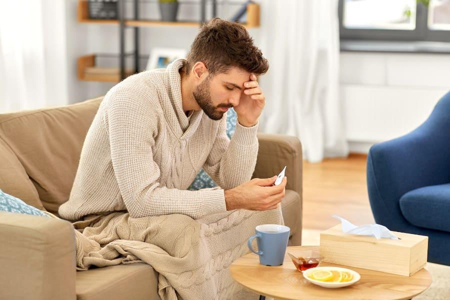 Mann sitzt auf einer Couch und hält sich die Stirn fest, während er auf ein Fiebertermostat schaut
