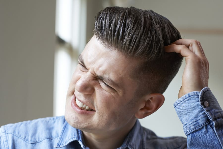 Junger Mann kratzt sich am Kopf als Haartransplantation Nebenwirkung
