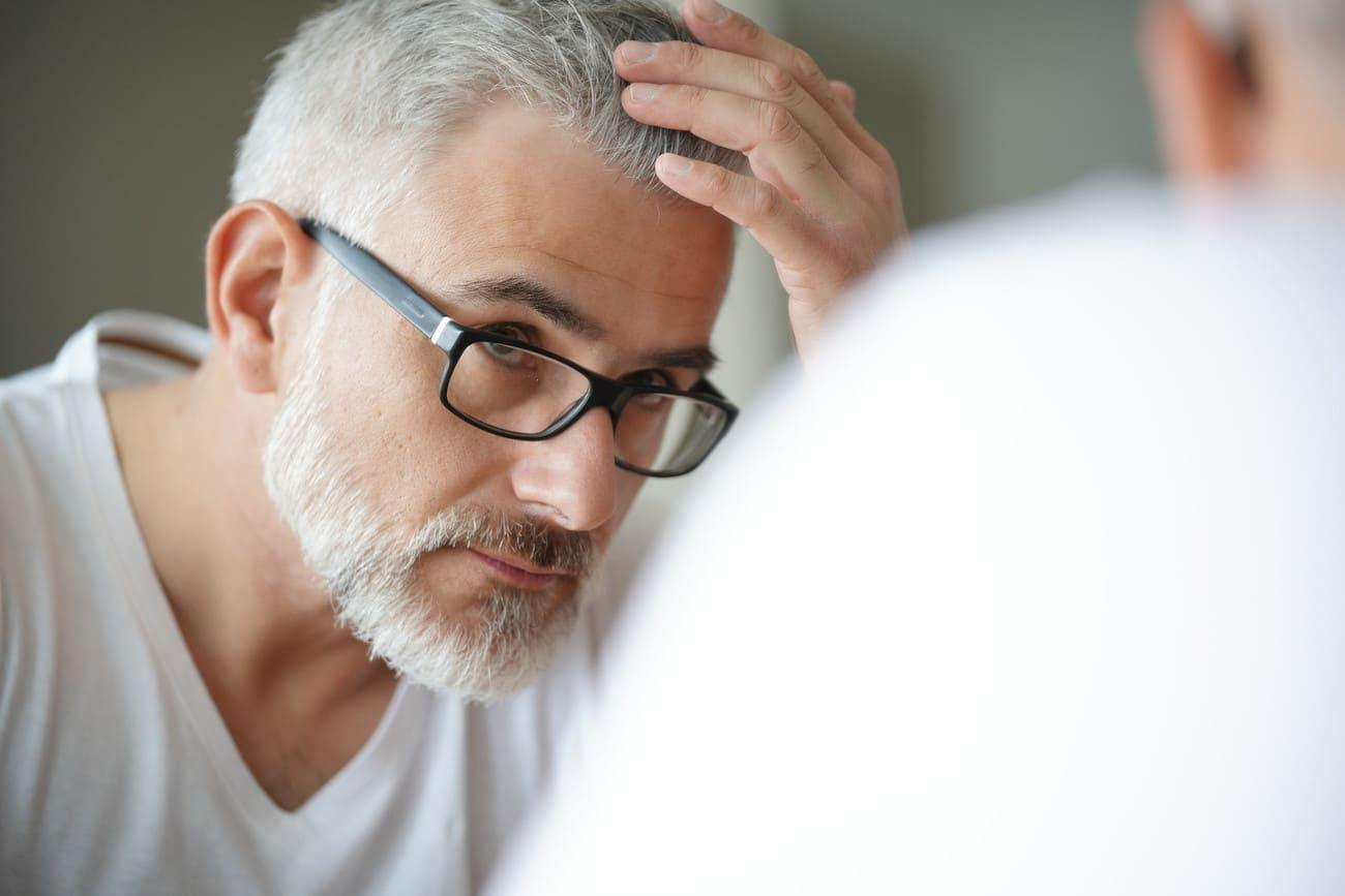 Mann mit grauem Haar guckt sich besorgt im Spiegel an