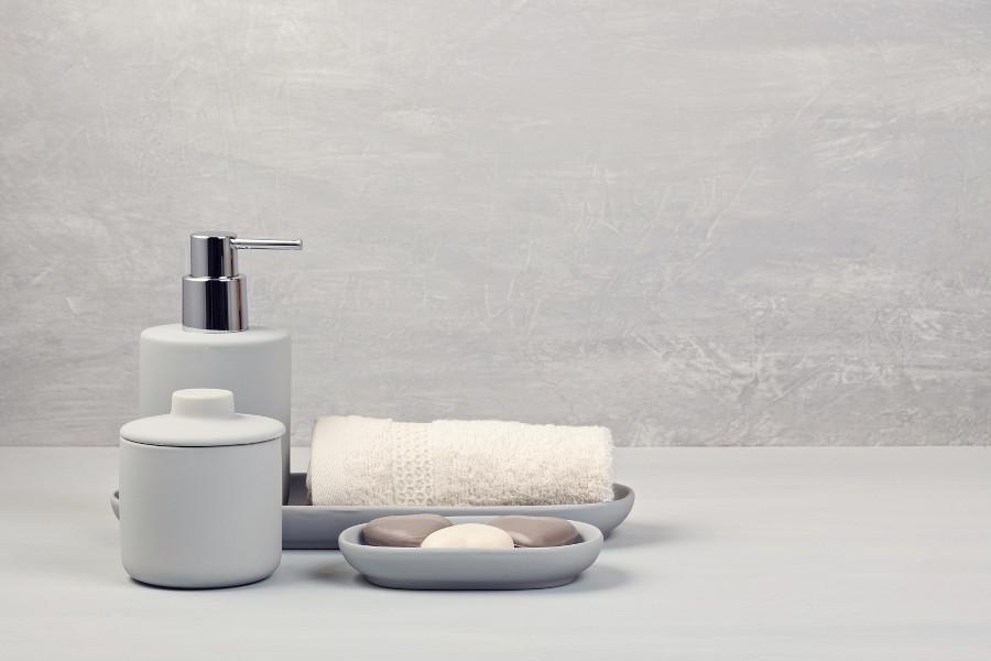 Shampoo und andere Hygienemittel stehen vor einem grauen Hintergrund