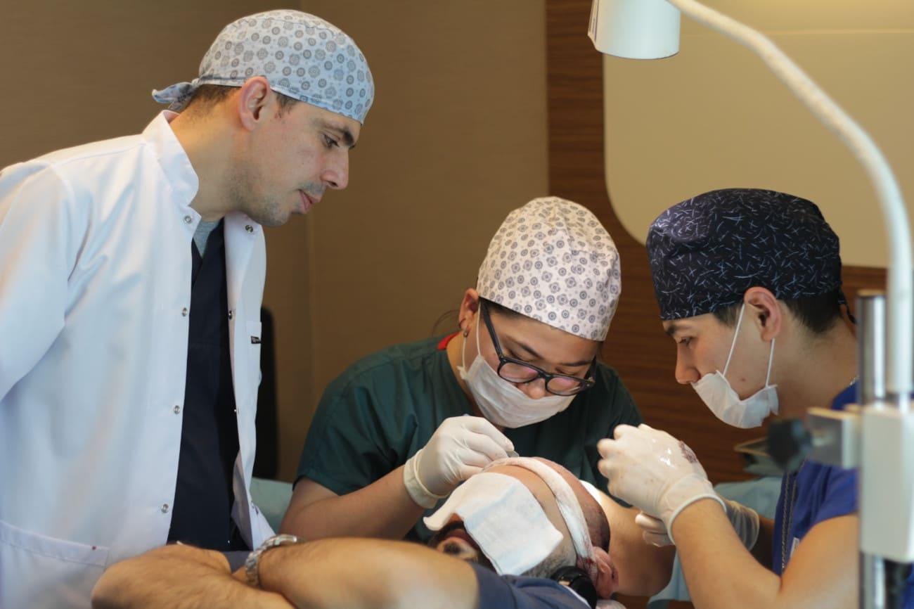 Drei Ärzte behandeln einen Mann mit Tuch vor dem Gesicht