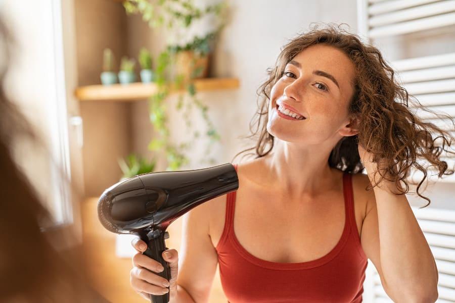 Junge Frau föhnt ihre Haare und hat Haarausfall