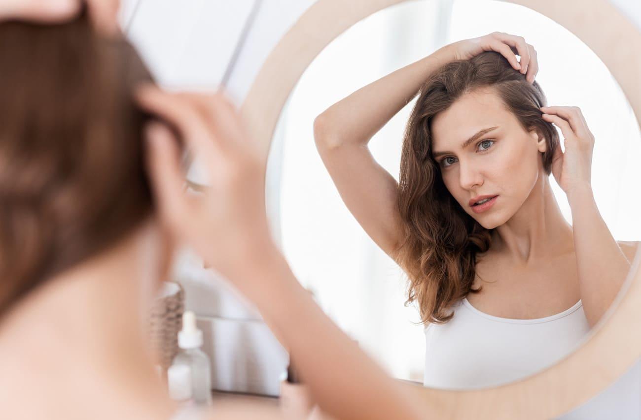 Frau steht vor einem Spiegel und fasst sich ins Haar