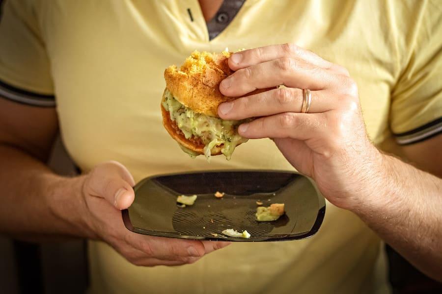Die Hände eines Mannes halten einen Burger und einen Teller