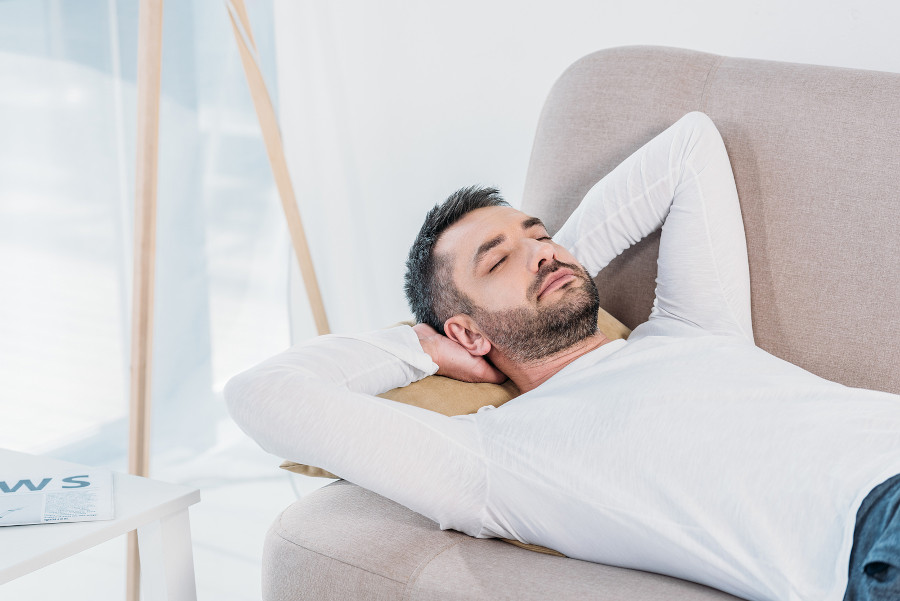 Mann liegt auf der Couch am Rücken - richtiges Verhalten nach einer Haartransplantation