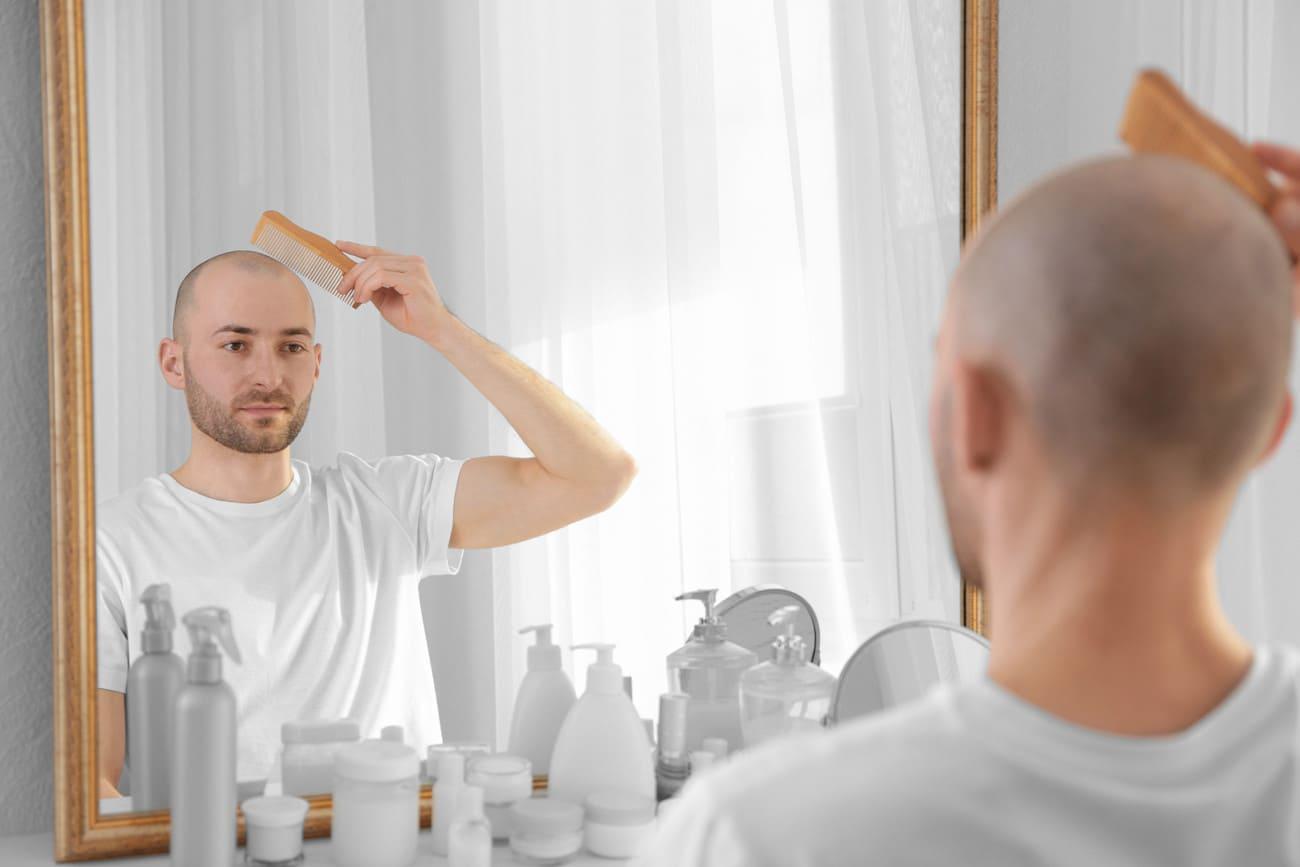 Mann mit Glatze kämmt sich die Haare vor einem Spiegel.
