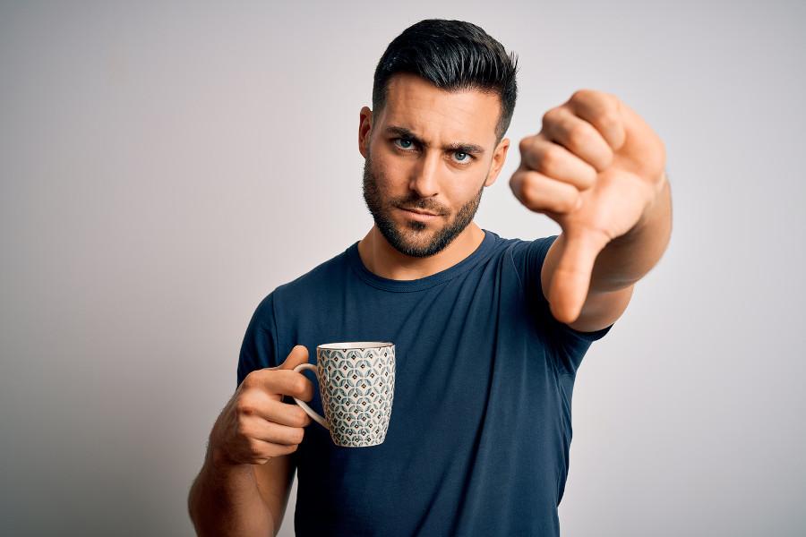Mann mit Kaffeetasse in der Hand zeigt Daumen nach unten - Kein Koffein nach der Haartransplantation damit Augen nicht geschwollen sind.