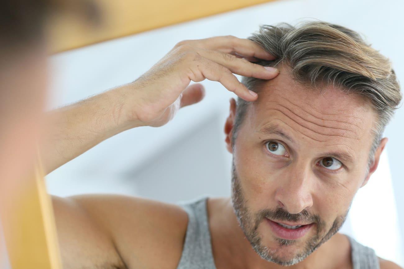 Mann fasst sich ins Haar und sieht sich dabei im Spiegel an.