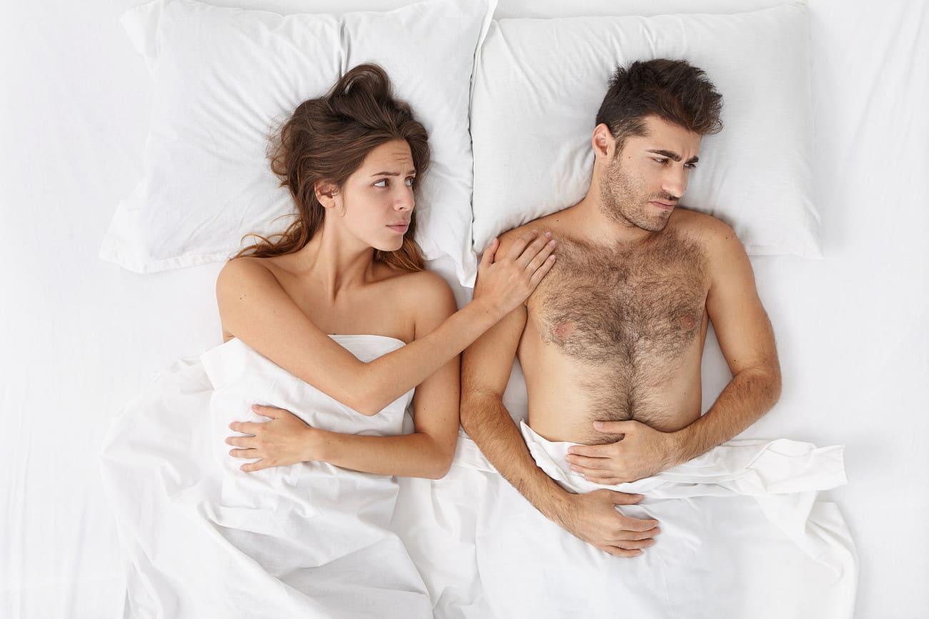 Mann und Frau liegen nebeneinander im Bett