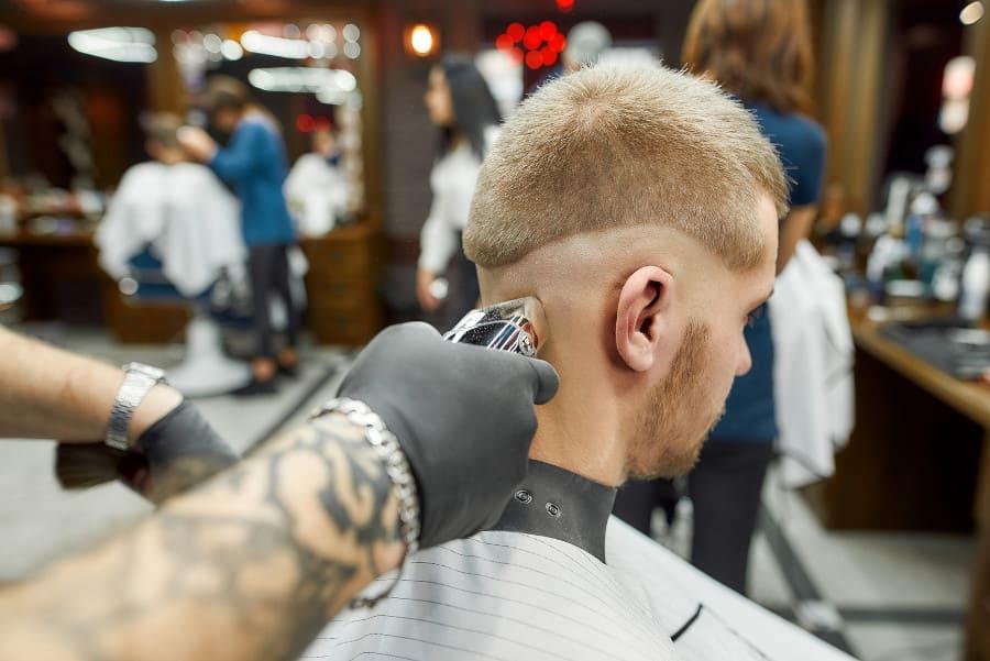 Mann mit Haarverlust im Nackenbereich bekommt beim Friseur einen Maschinenhaarschnitt