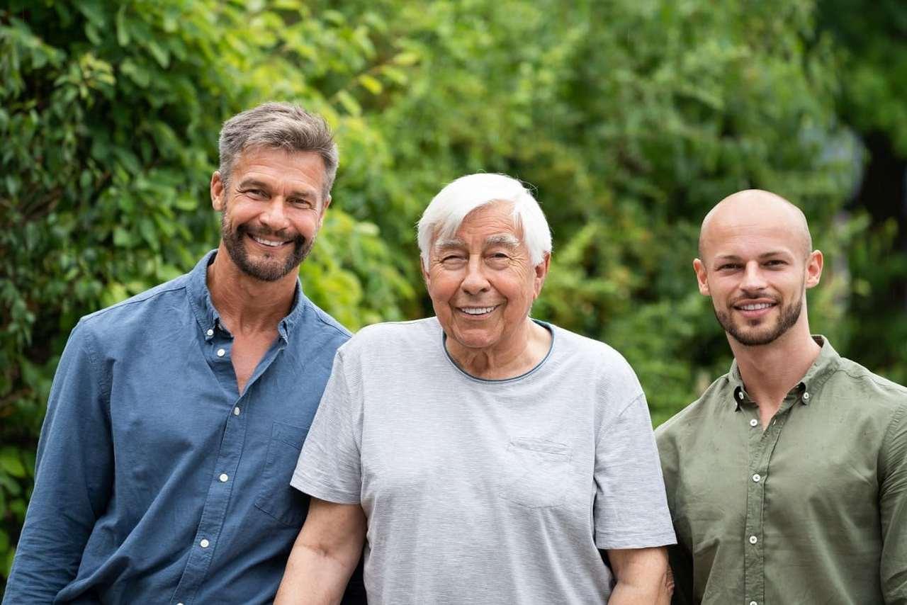 Drei Männer mit unterschiedlichem Alter stehen nebeneinander.