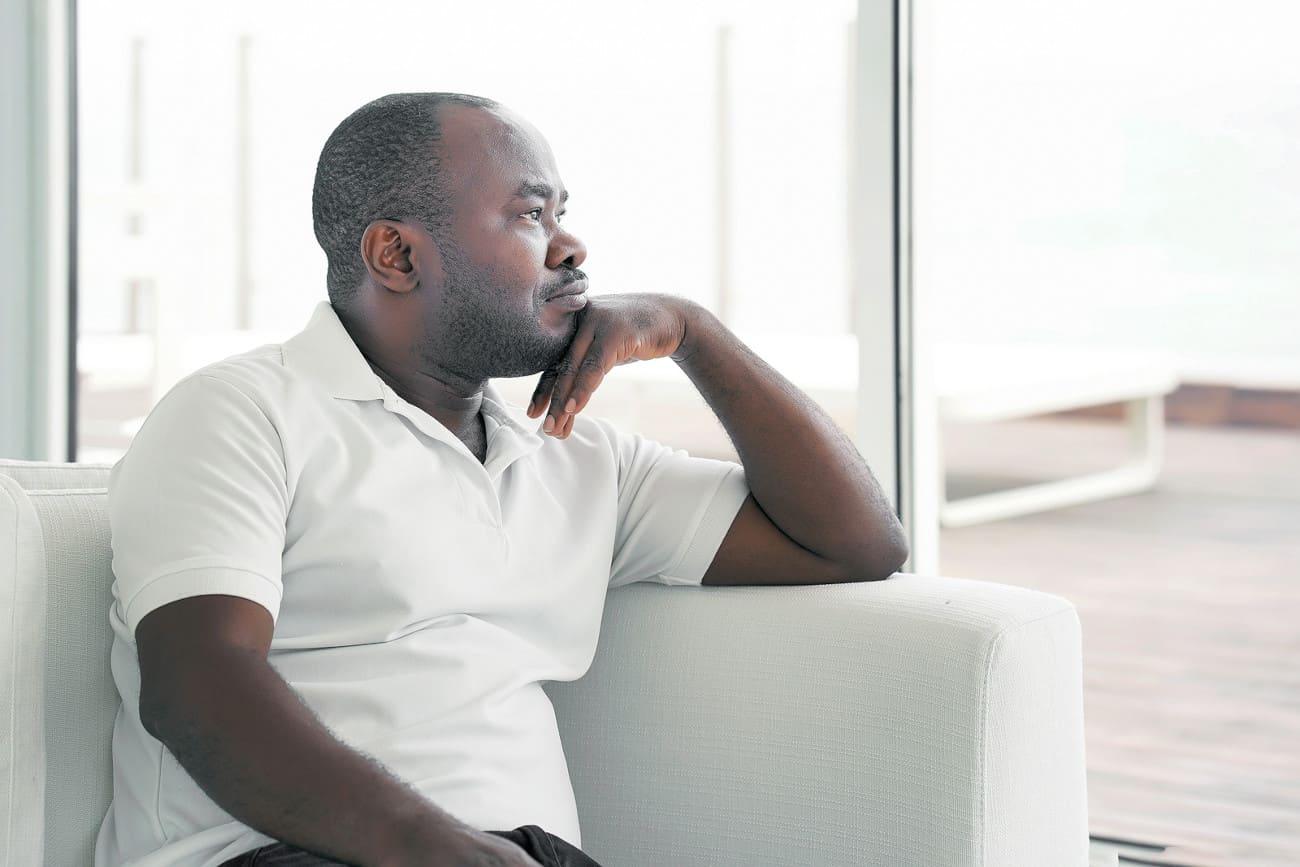 Mann mit Haarausfall sitzt auf der Couch.