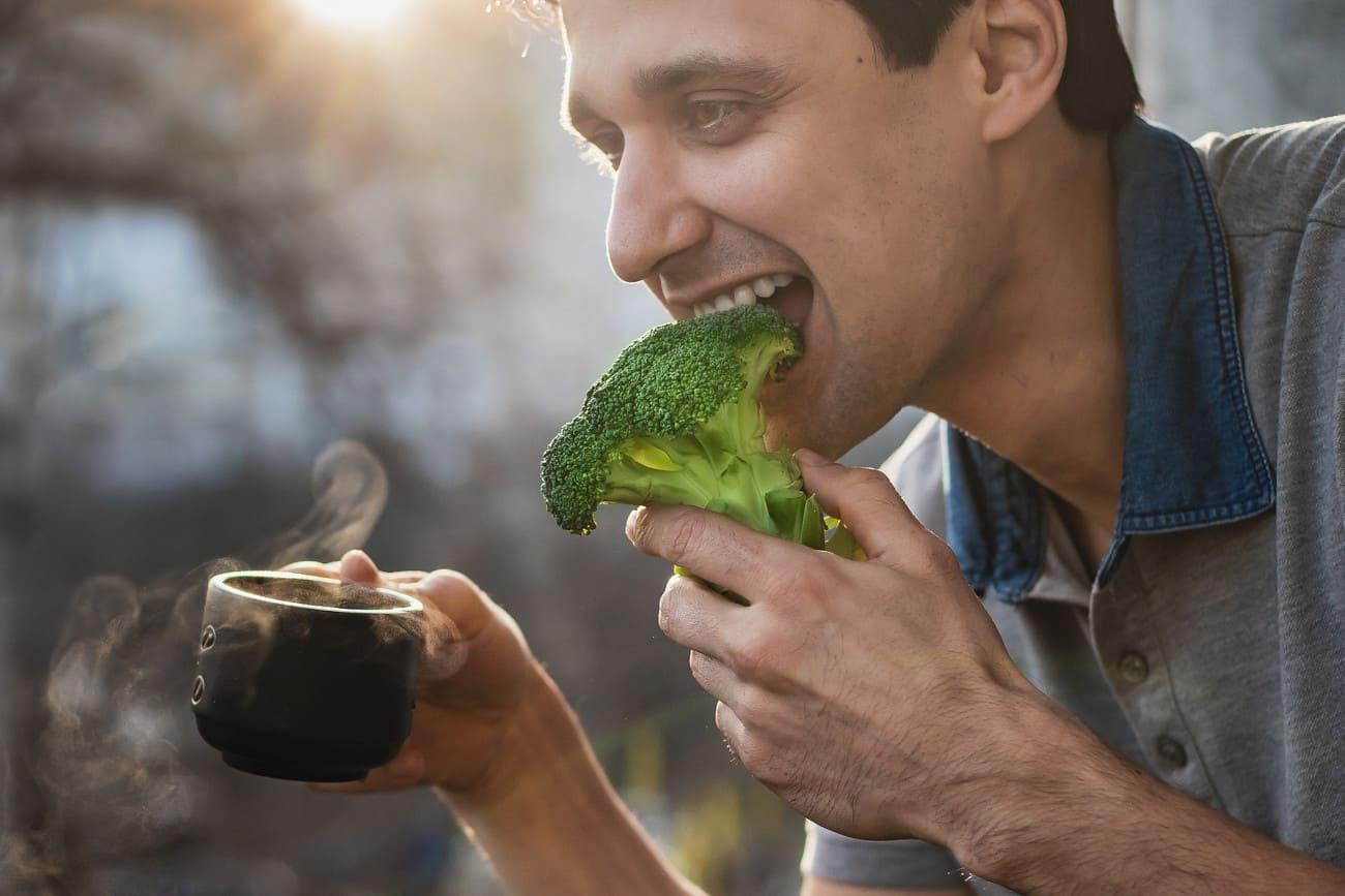 Mann isst Brokkoli und hält dabei einen Tee in der Hand.
