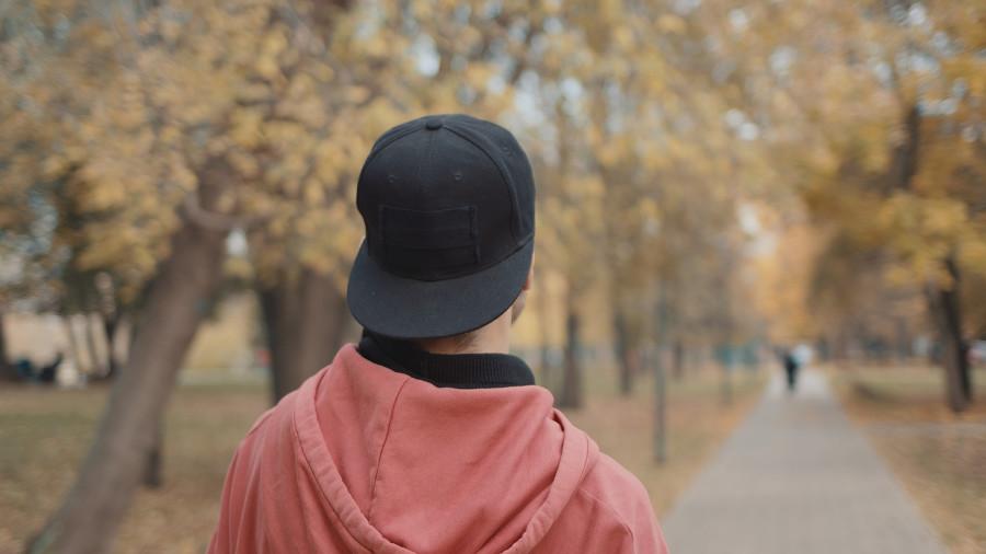 Mann mit Kappe von hinten, nachdem er sich nach einer Haartransplantation den Kopf gestoßen hat.