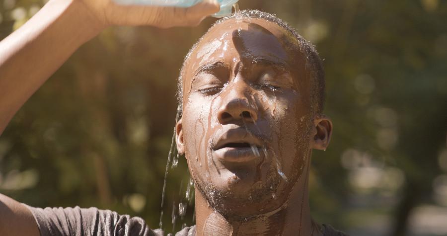 Junge Mann gießt Wass auf sein Gesicht.